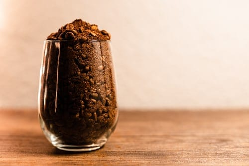 A glass full of non-uniform coffee beans and grounds