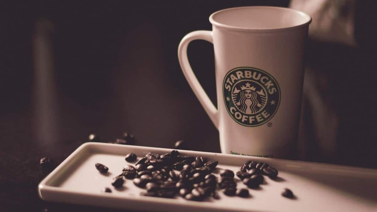 The most popular brand Starbucks coffee along with coffee beans on a tray.