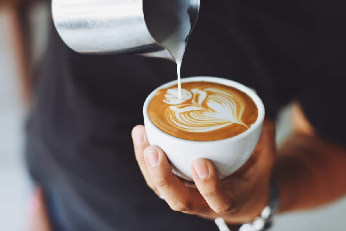 A man pouring keto-friendly cream in their coffee