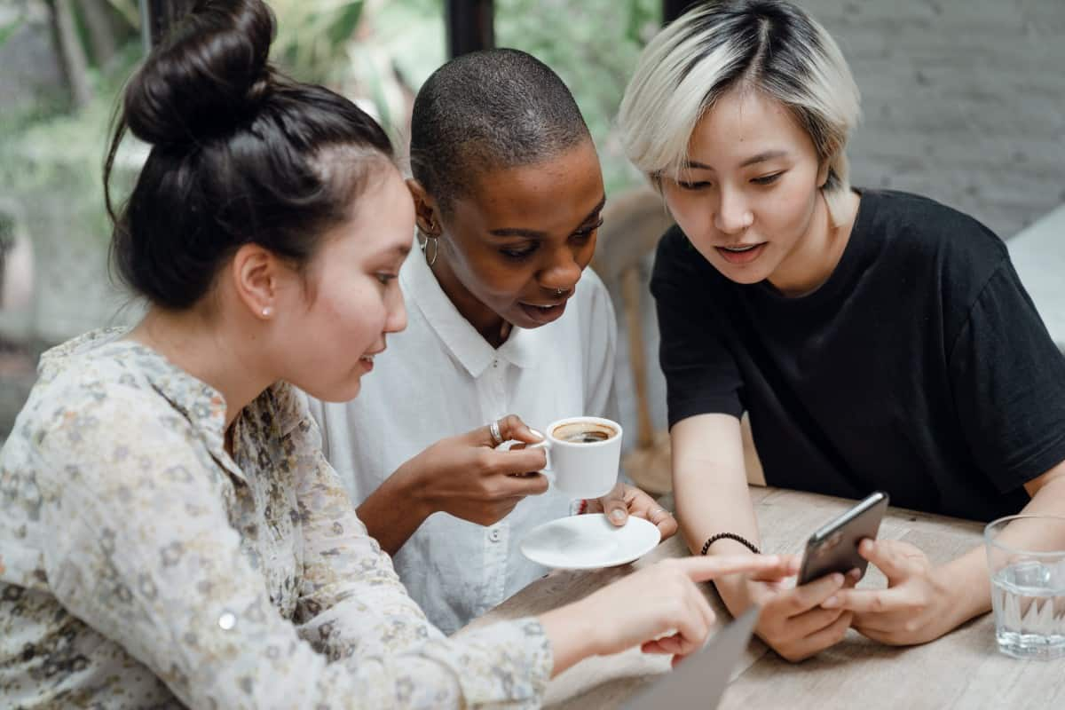 three woman learning about keto-coffee on a phone while one holding coffee cup in their hand
