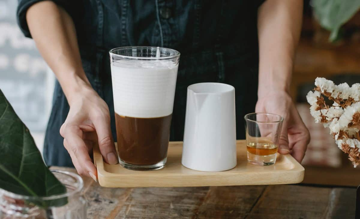 Person serving liquor, coffee and milk in a small tray at a café