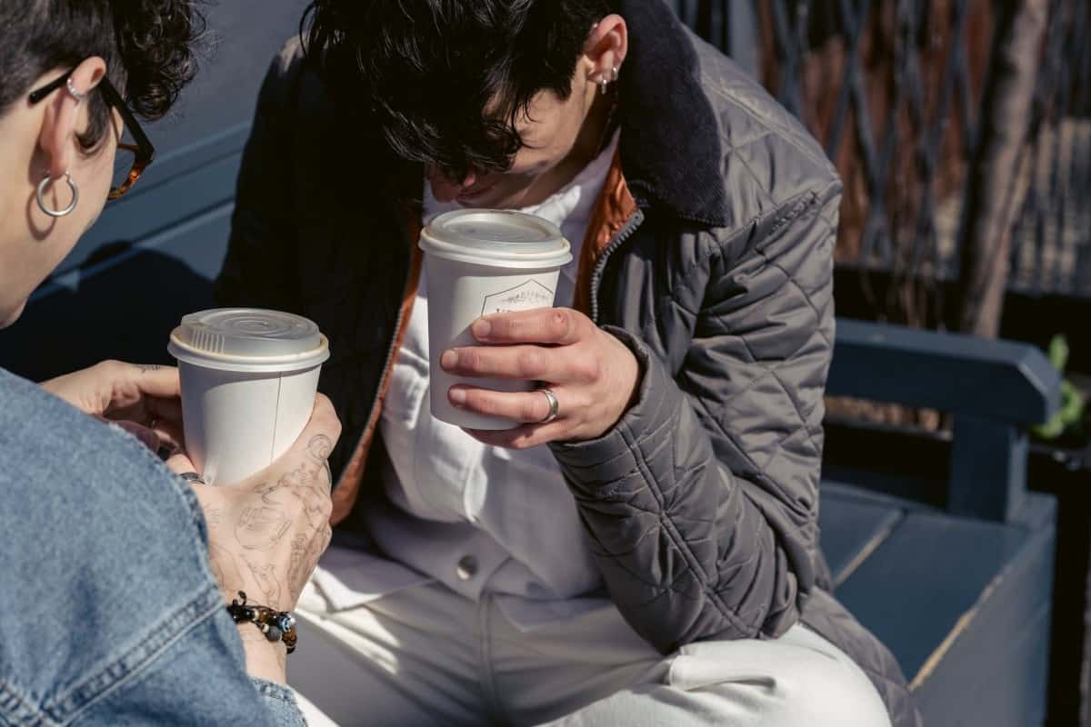 Two in individuals sitting on a bench and enjoying their coffee