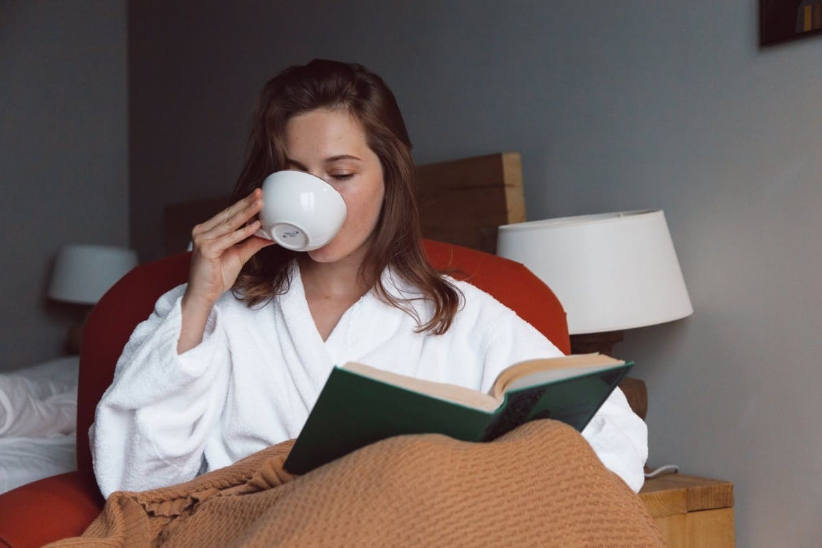Woman in a white robe drinking coffee from a white mug while reading a book with green hardcover.