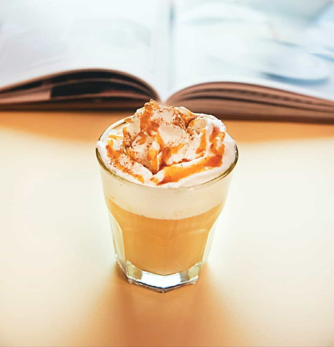 Iced caramel macchiato with whipped cream.