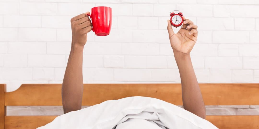 A person holding an alarm clock and a cup of coffee in bed