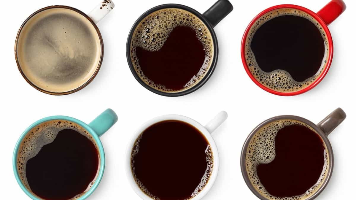 An above view of coffee in different colored mugs