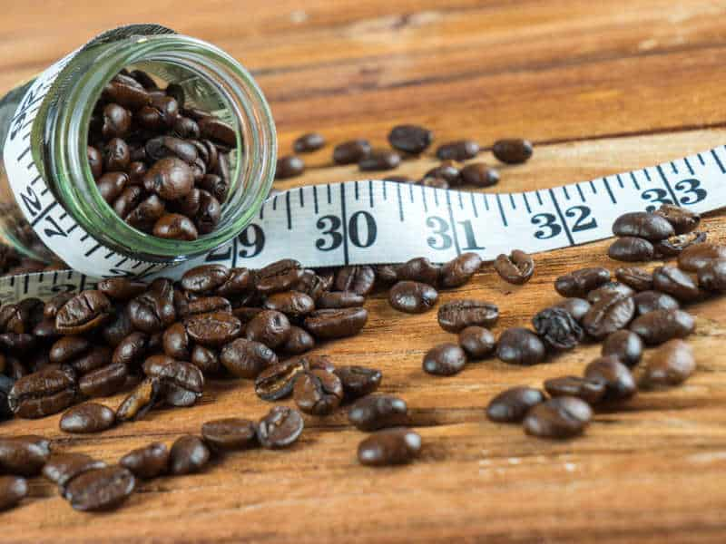 tape measurer wrapped around a jar of coffee beans spilt on the ground