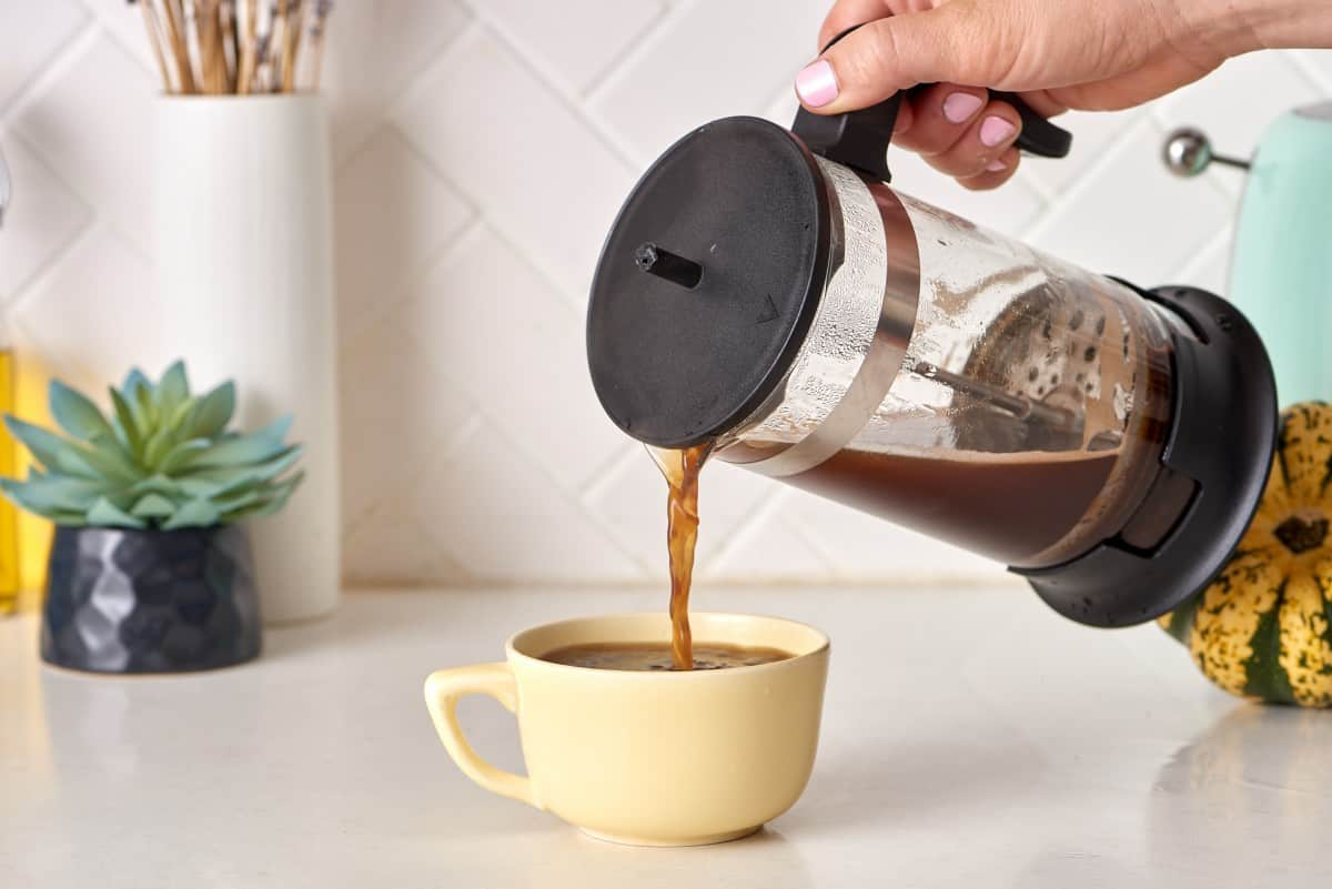 coffee being poured into a coffee cup