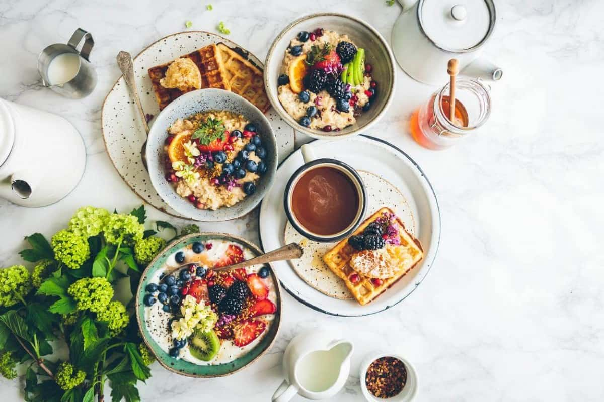A healthy breakfast containing fruits, bread, waffle and coffee.