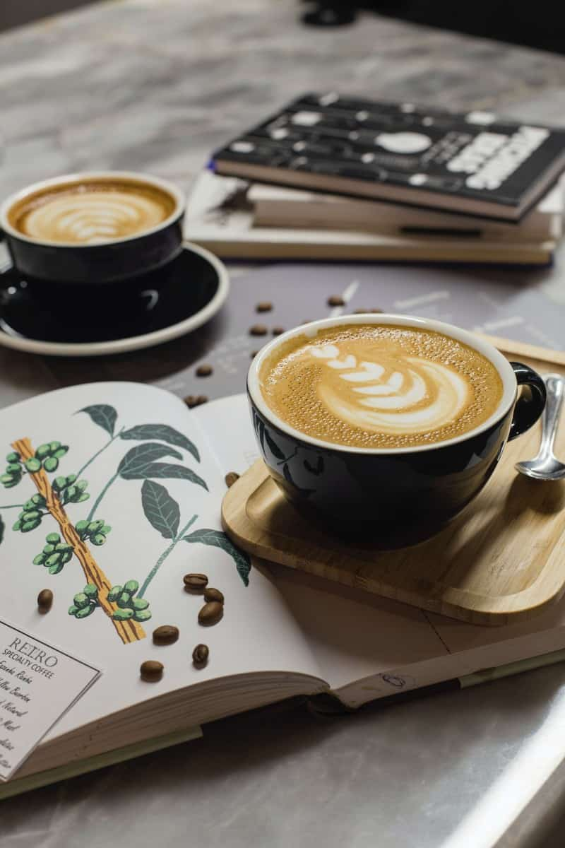 two cups of cappuccino with an open book and some scattered coffee beans