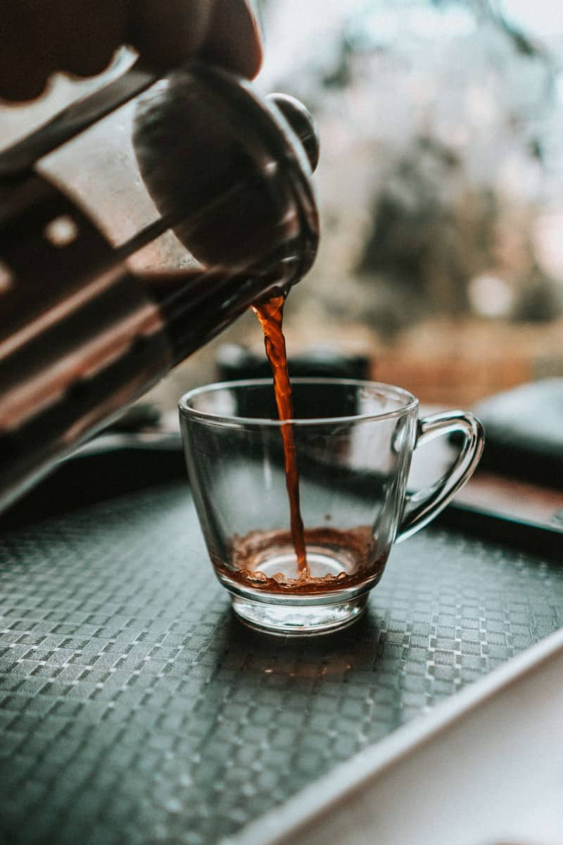 pouring black coffee from the kettle into a glass cup.