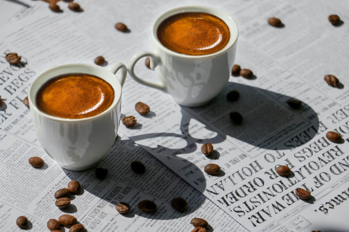two tiny cups of coffee on top of a newspaper littered with coffee beans