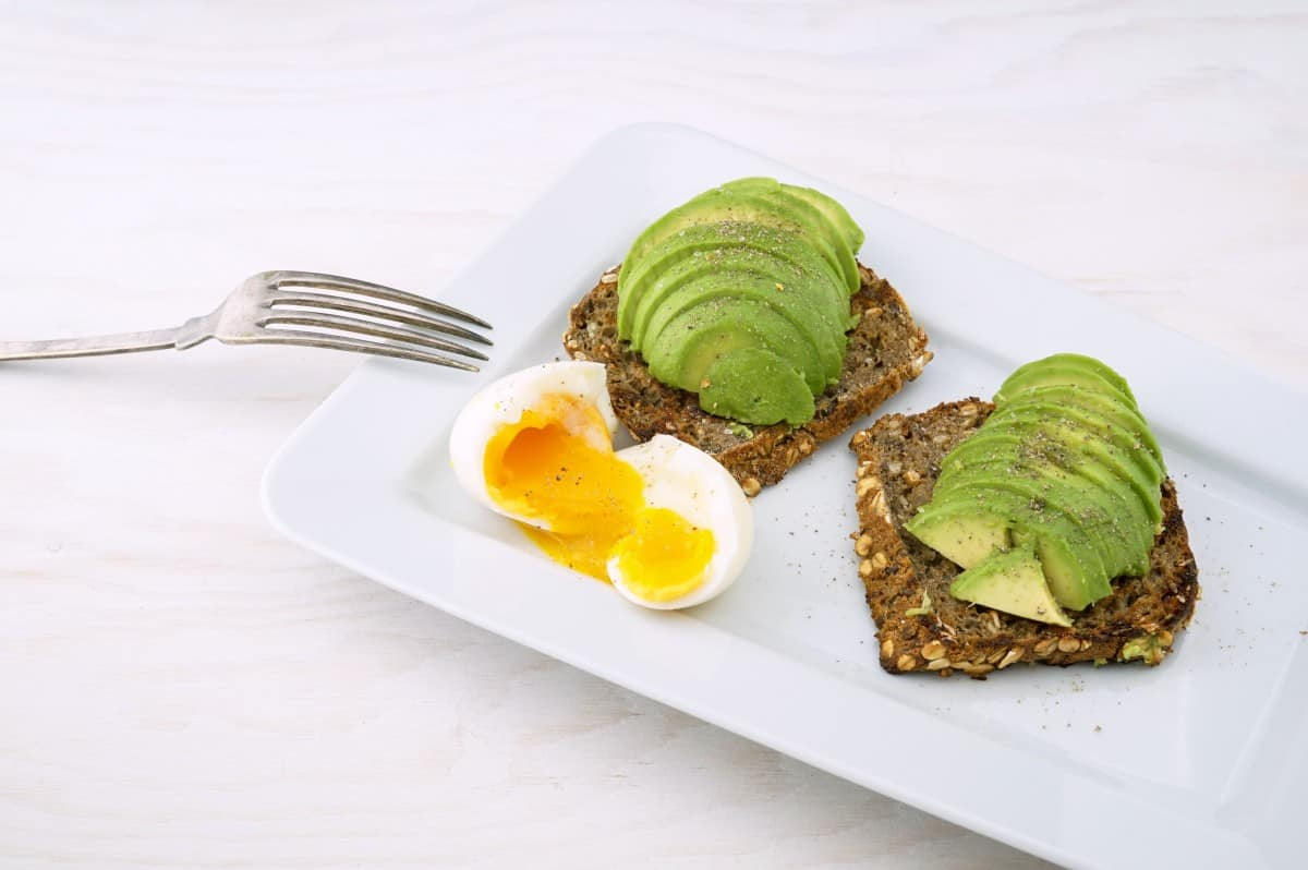 wholewheat bread avocado toast with soft boil egg on a white platter and fork on the side.