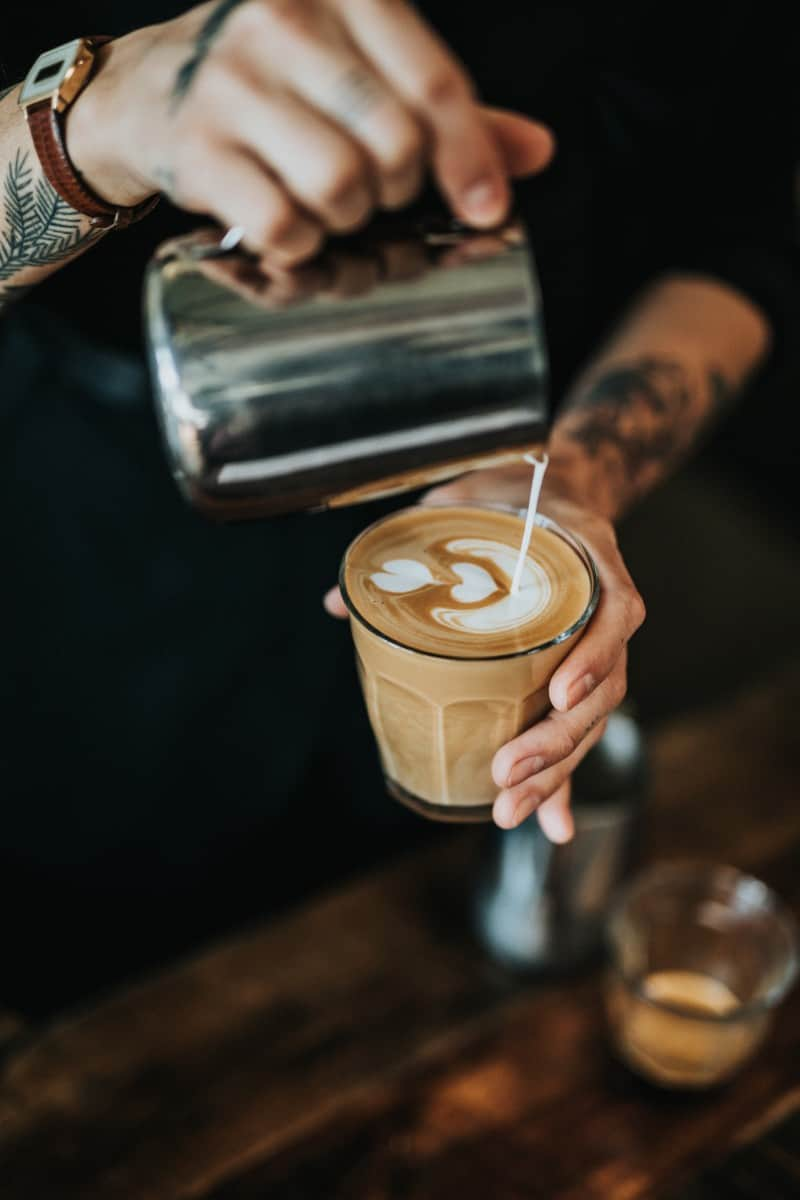 a barista making a latte and pouring warm milk to make latte art