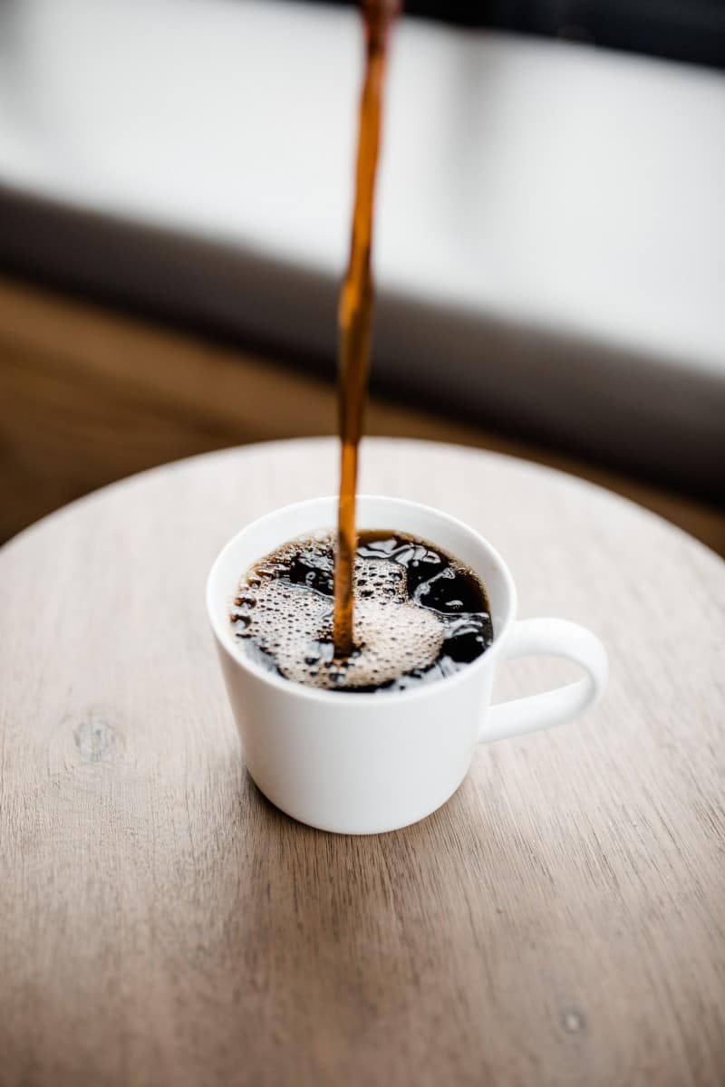 black coffee being poured in a small white coffee cup.