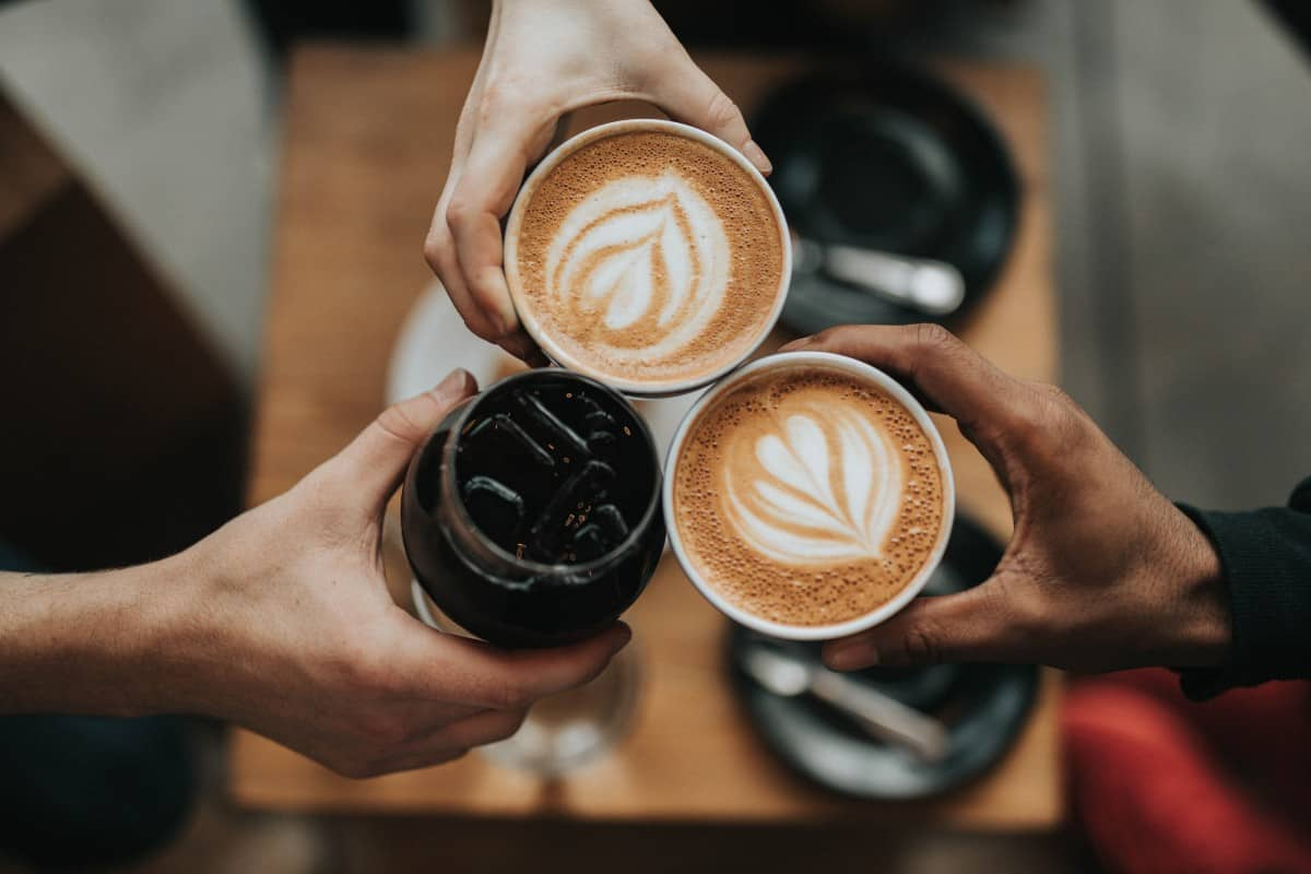 3 people cheering with 3 different kinds of coffee in their respective hands