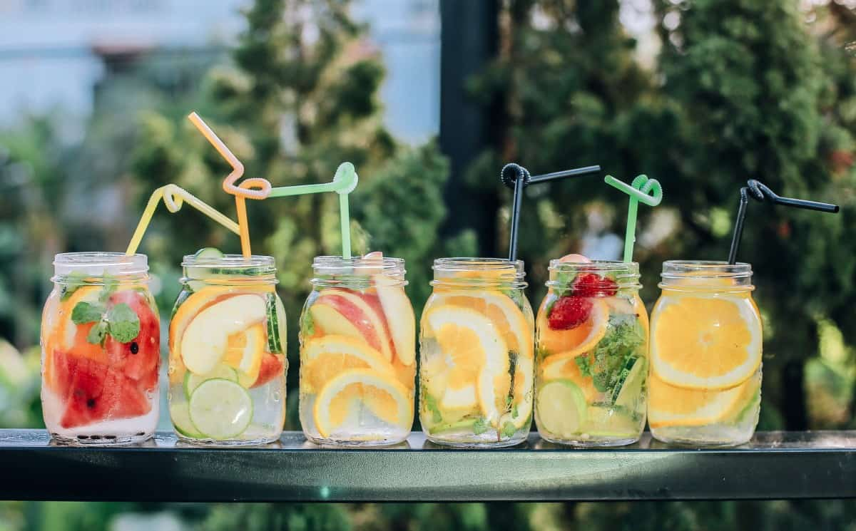 6 mason jars filled with various fruit juices and straws
