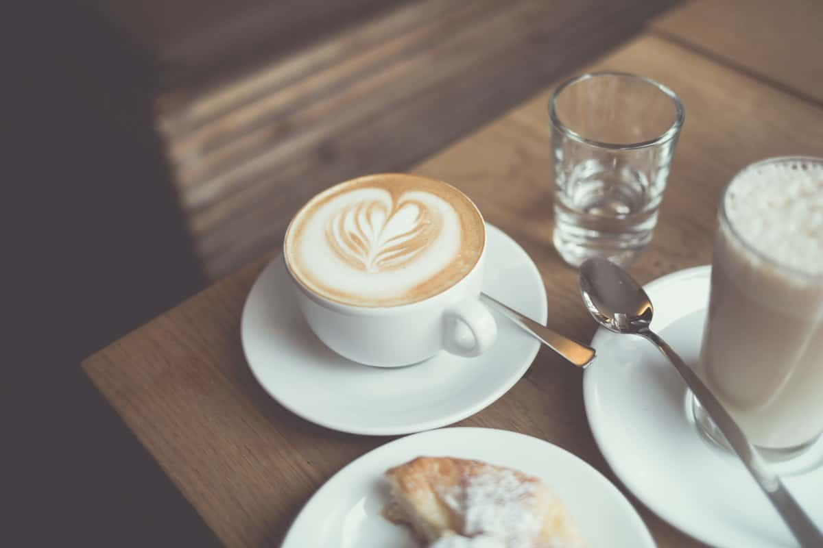 a cappuccino cup kept on the table with some sweet treats.