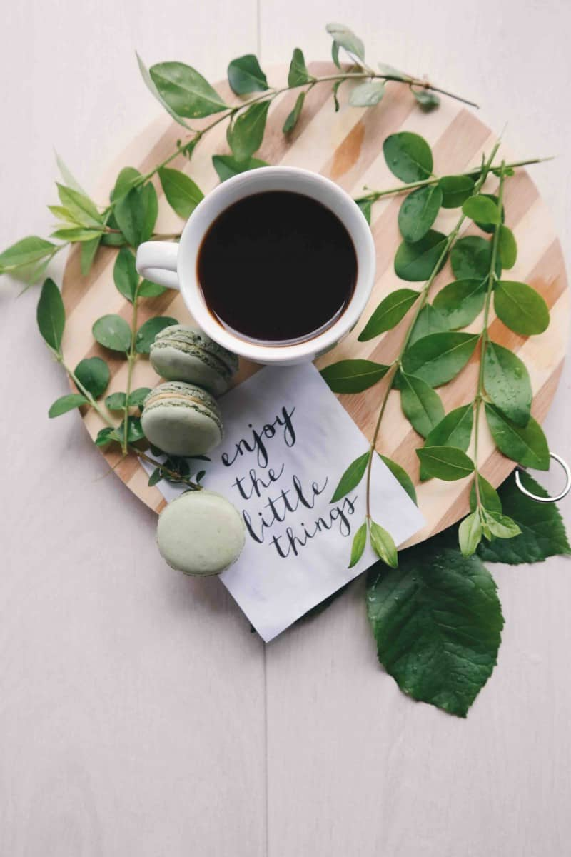 a small cup of black coffee with plants and green macaroons. and some green leaves around it with a note.