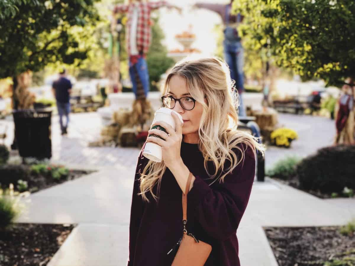 a blonde girl with glasses sipping on a starbucks coffee in a park