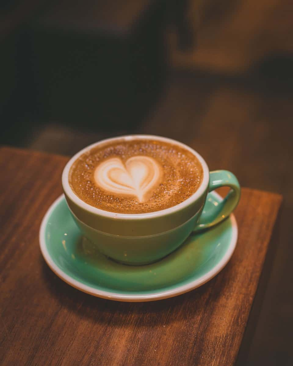 a green cup of coffee with warm cappuccino
