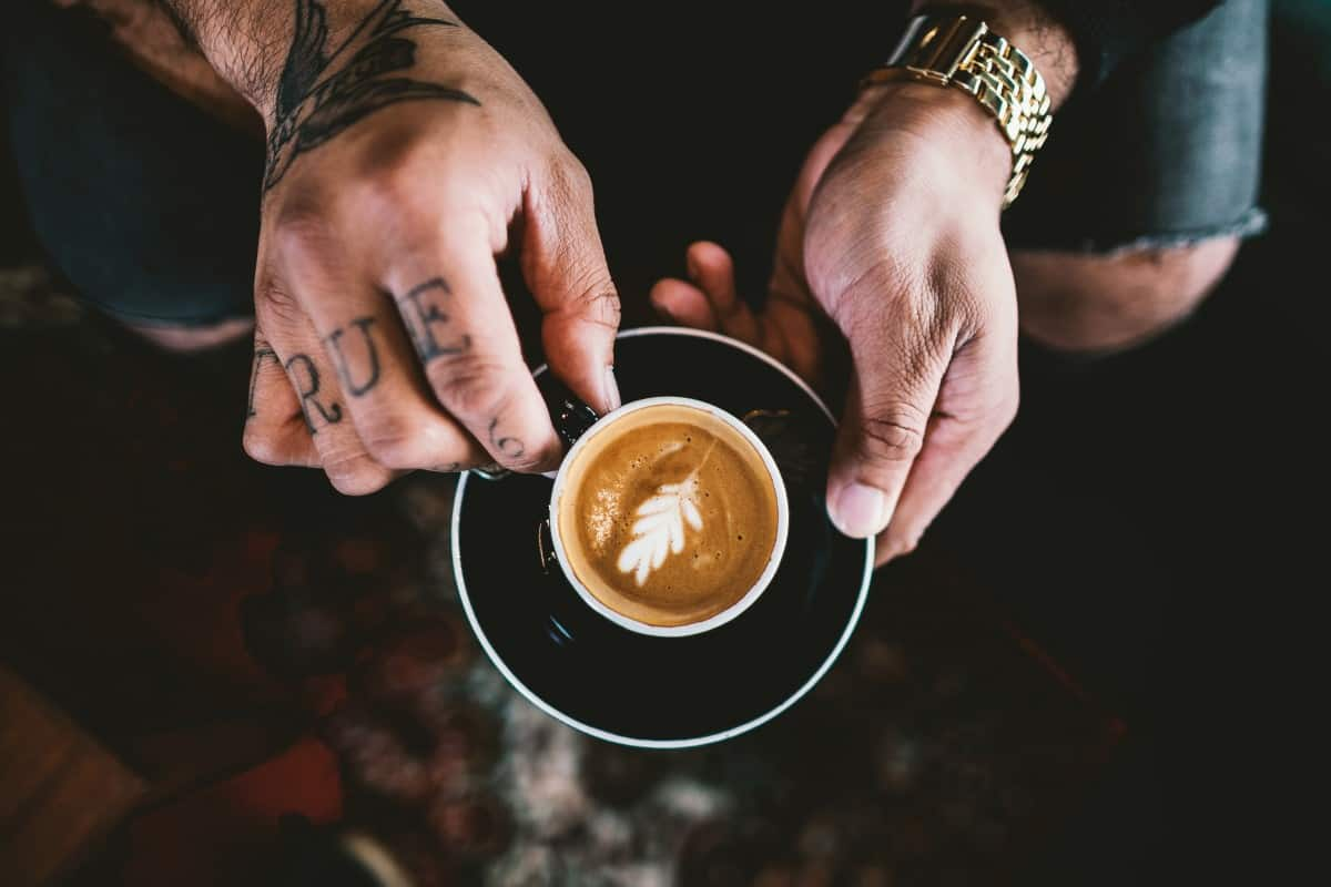 a man with tattoos holding a cup of coffee in his hands