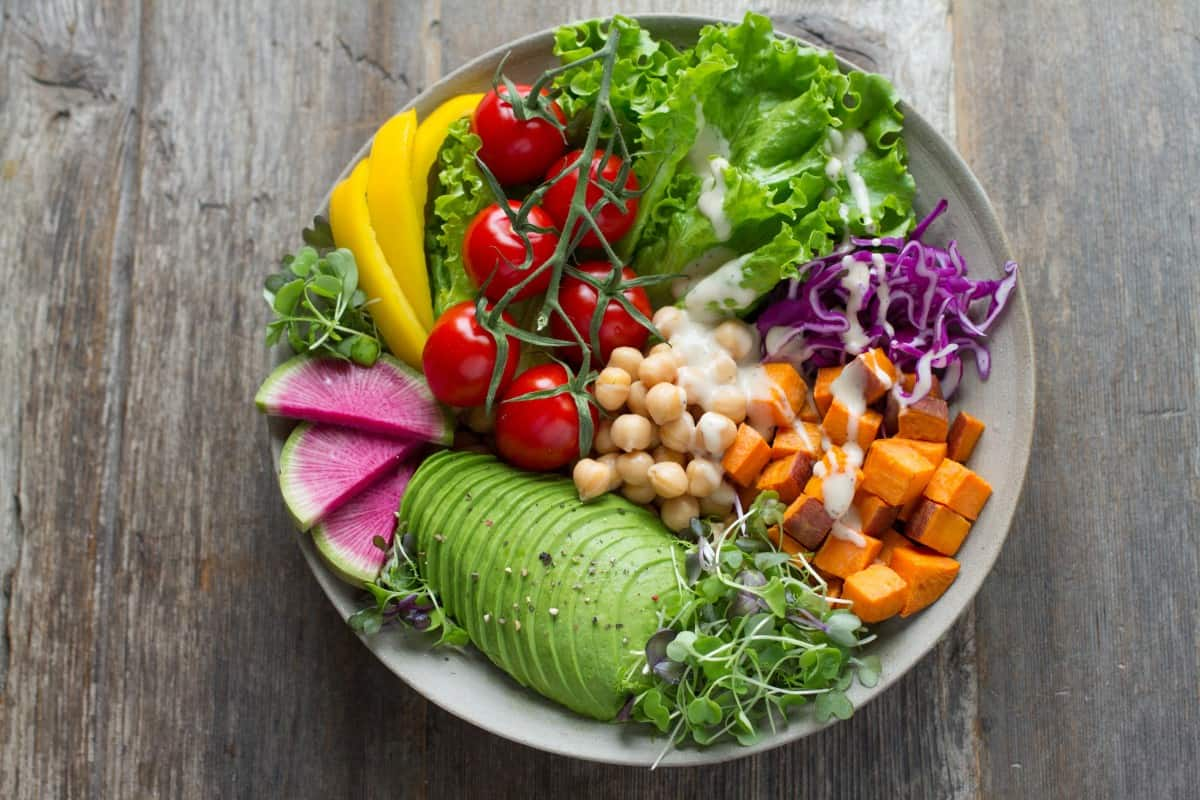 a bowl filled with healthy foods like avocado, fig,squash,chickpeas, capsicum,tomatoes and iceberg