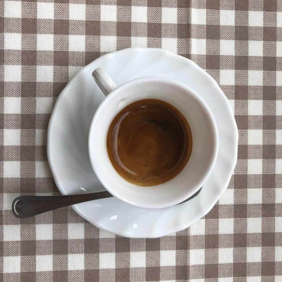 a cup of coffee taken from above on a patterned table cloth