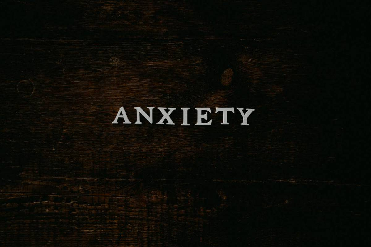 the letters spelling anxiety laid out on a wooden platform