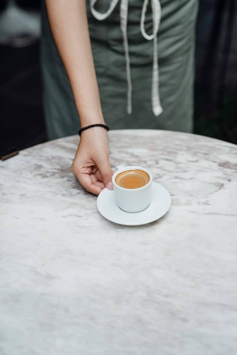 a barista serving a cup of coffee