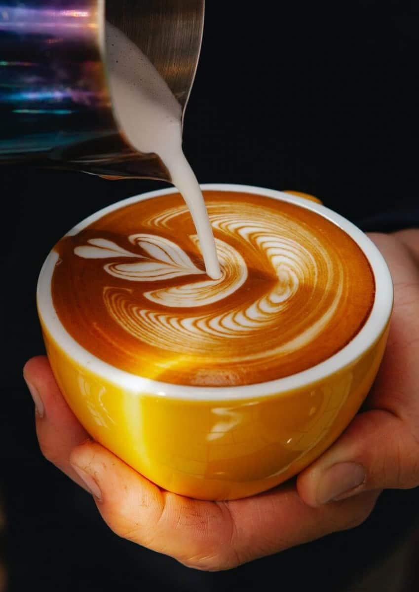 Cream being poured in a cup of coffee