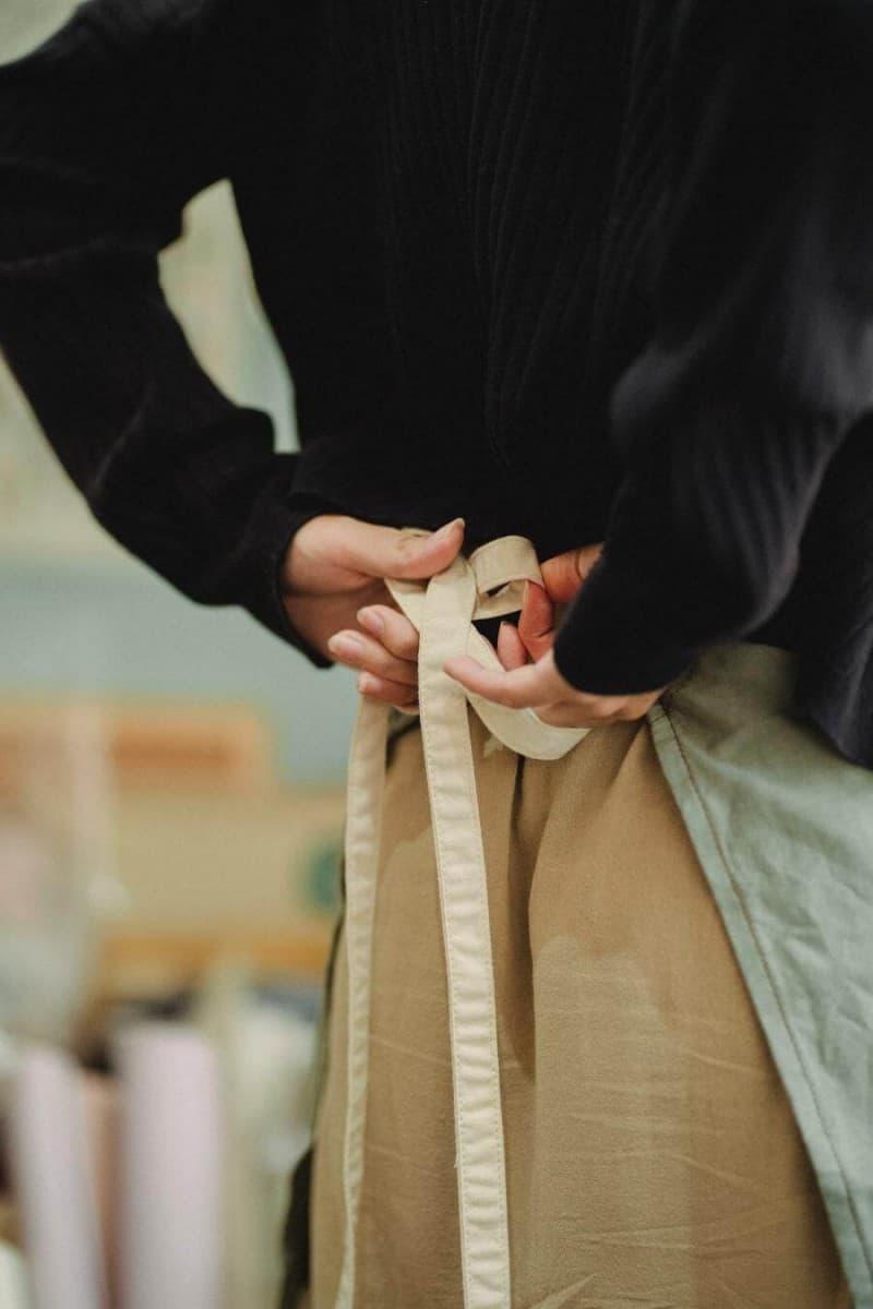 A barista tying their apron