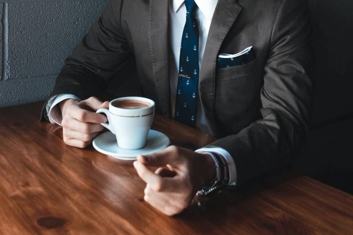 A man in a suit having a cup of coffee