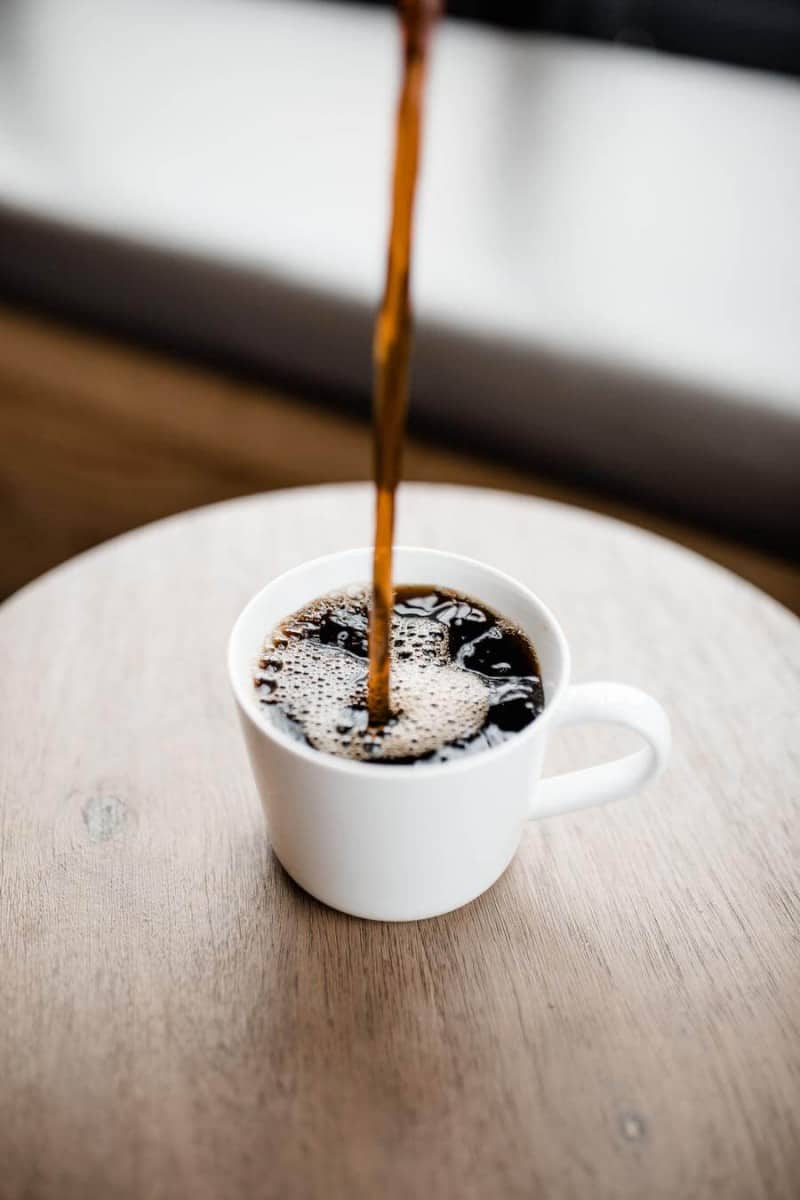 Someone pouring coffee into a cup