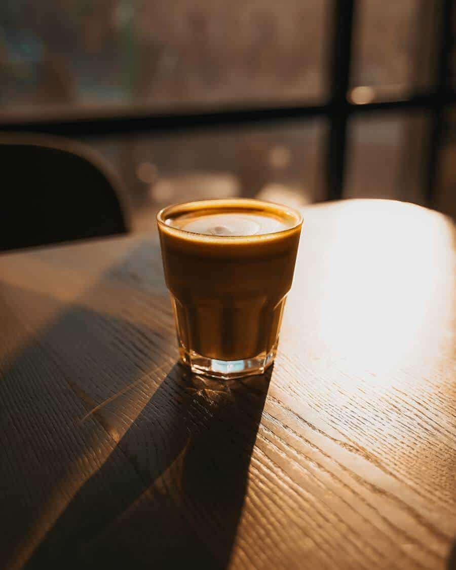 A glass of cortado placed on top of a wooden table