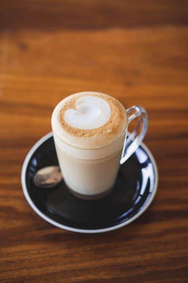 A latte in a clear mug on a small plate