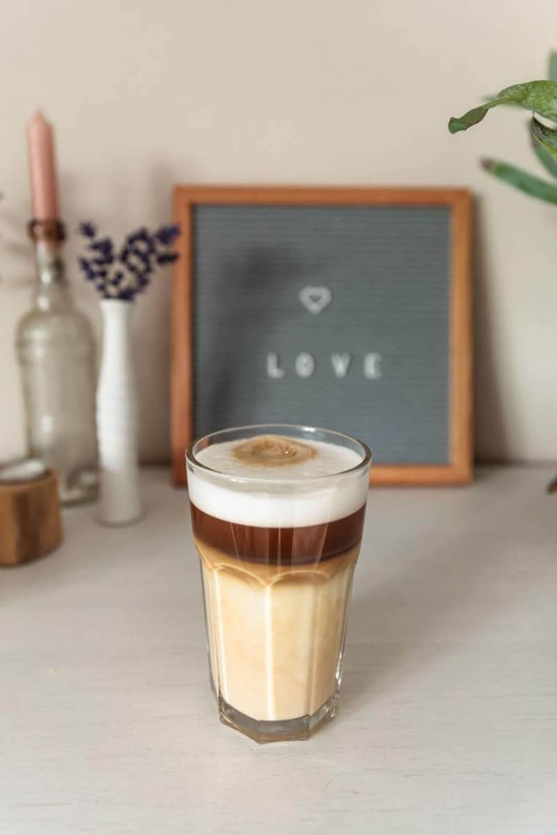 Coffee with a foam of milk on top in a clear glass