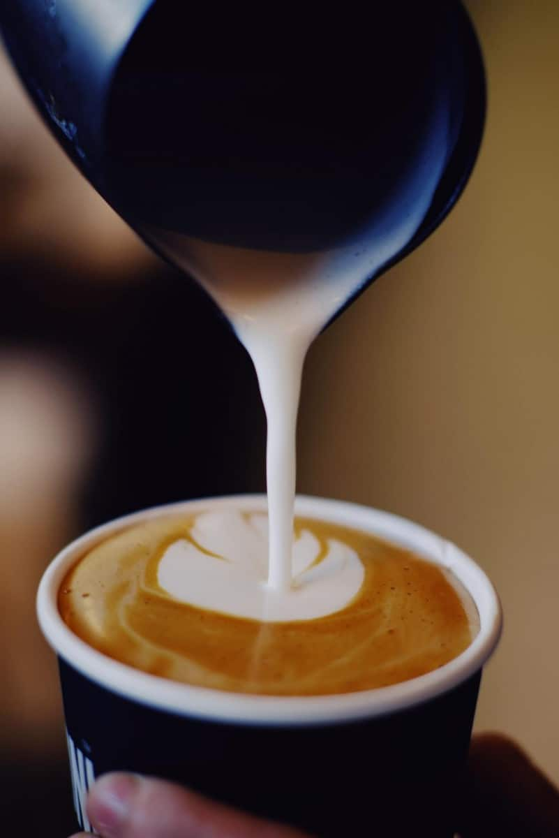 creamer being added to a cup of coffee
