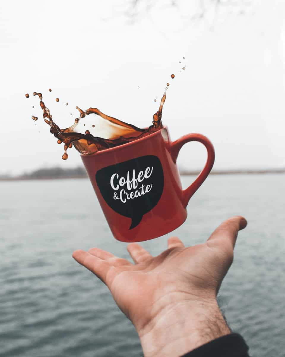 a red mug of black coffee being thrown in the air