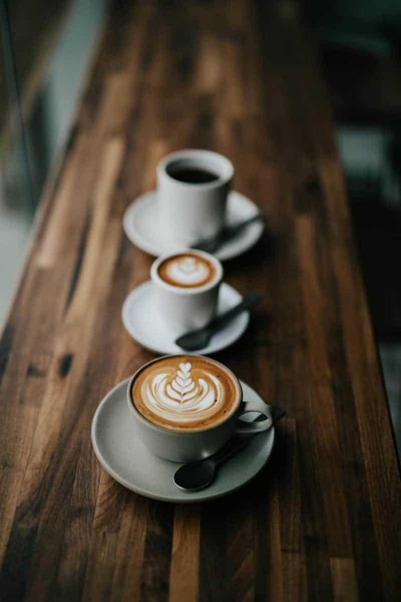 coffee lined up on a wooden ledge