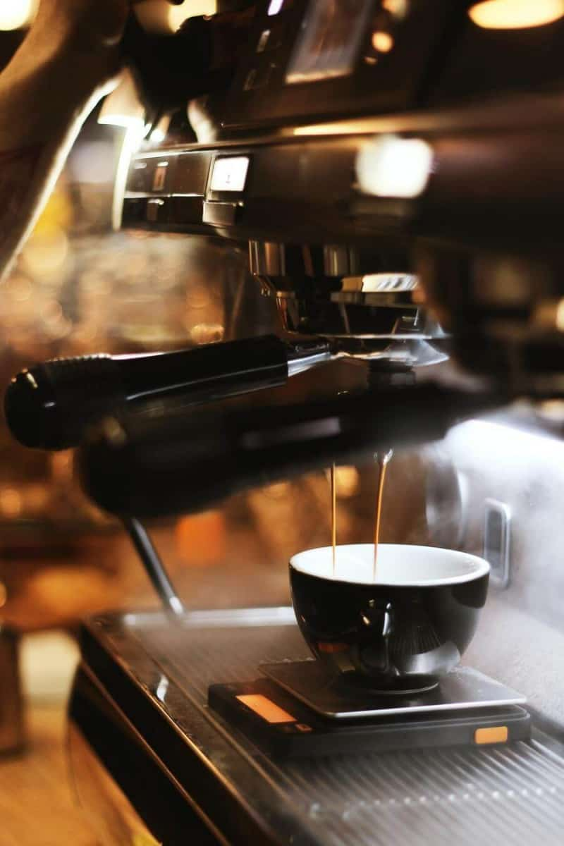 a cup of coffee under a coffee machine