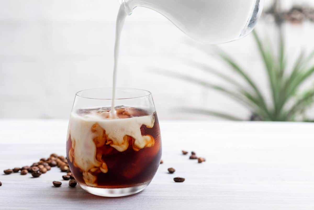 Milk being poured into a clear glass of coffee surrounded by coffee beans.