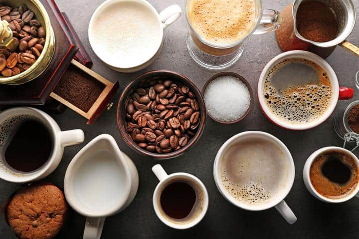 An assortment of cups of coffee along with coffee beans and creamers