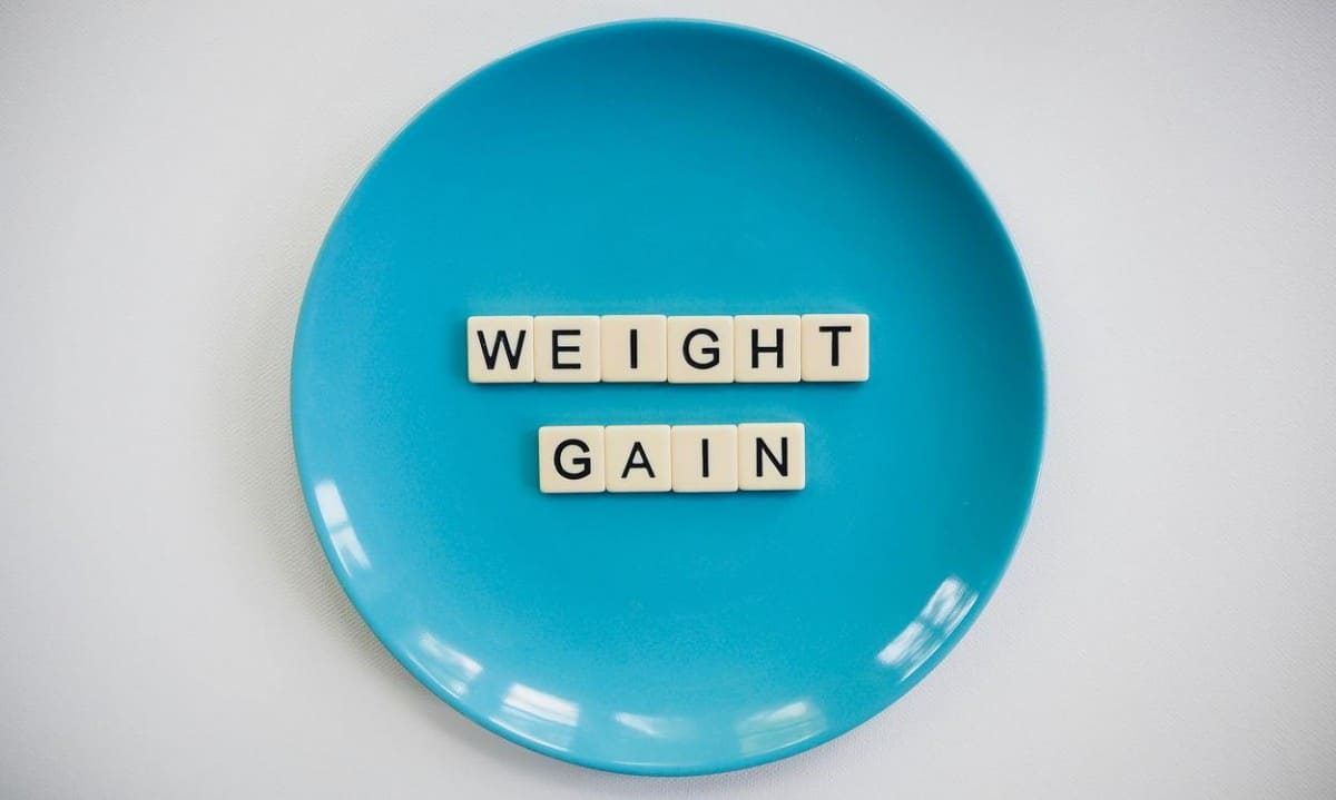 the words weight weight gain on a blue plate