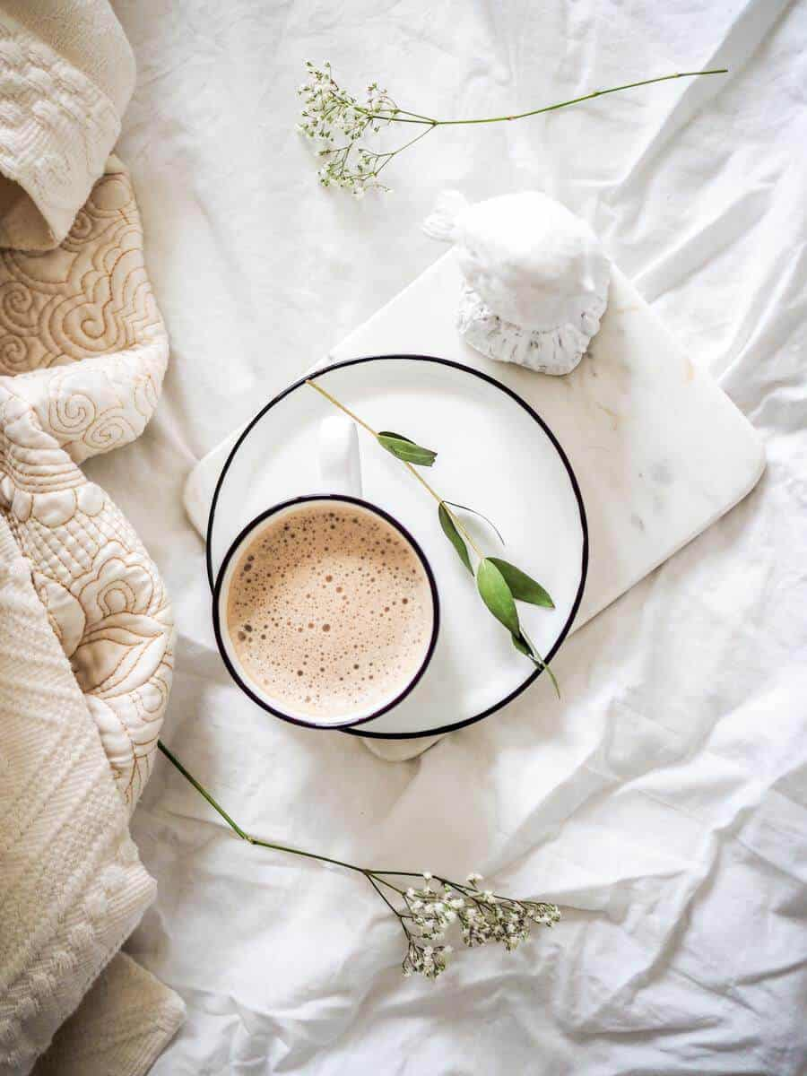 cup of coffee on white sheet