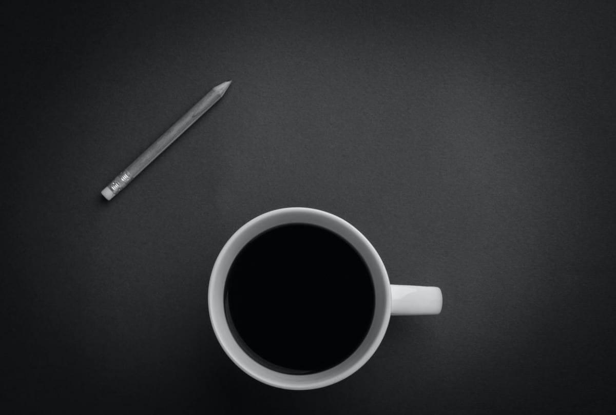 Black coffee next to a pencil