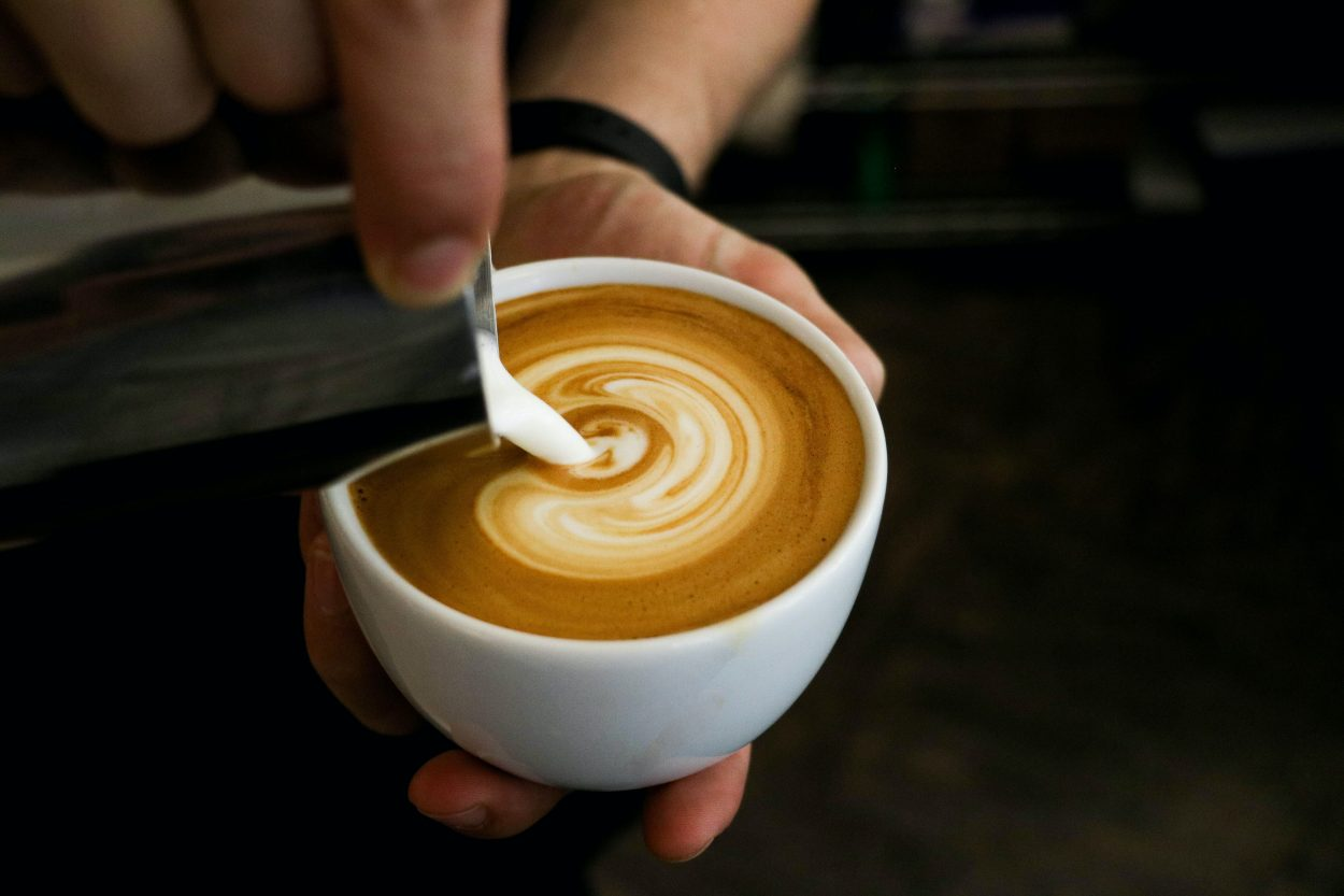 a barista making a cup of cappuccino