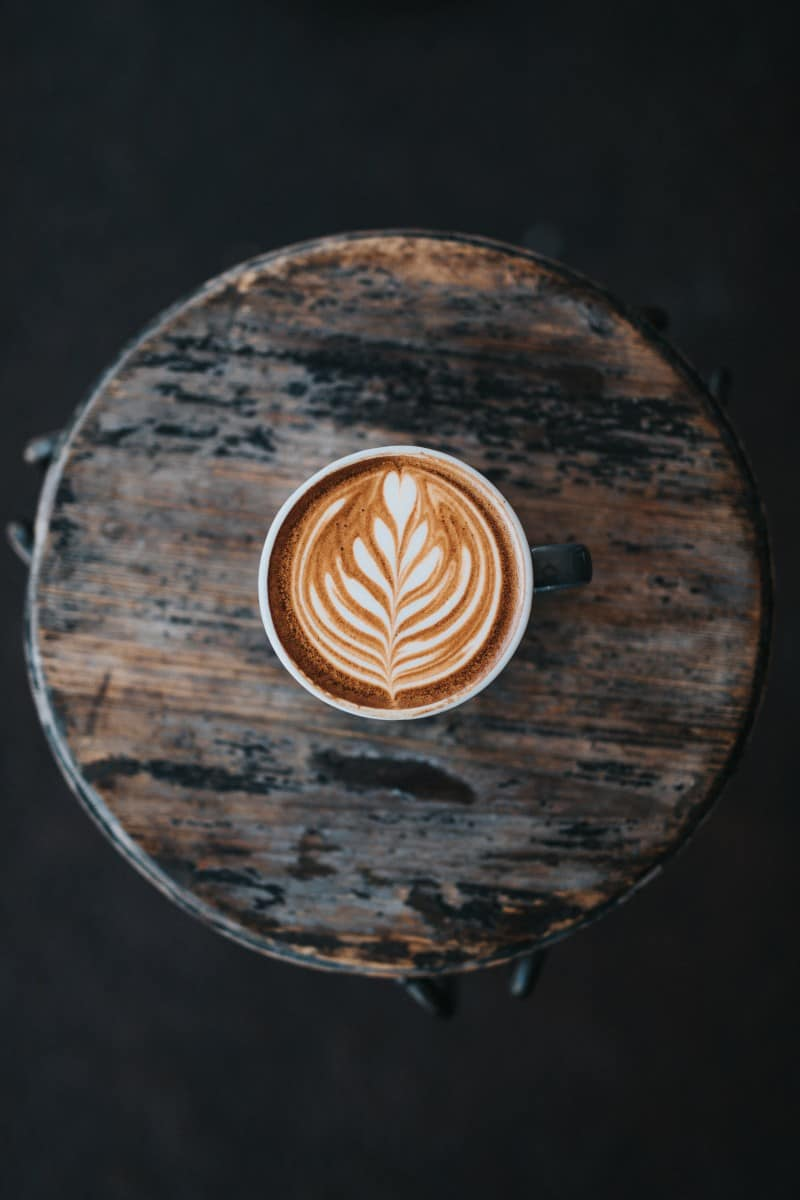 a cup of mocha on a wooden coffee table
