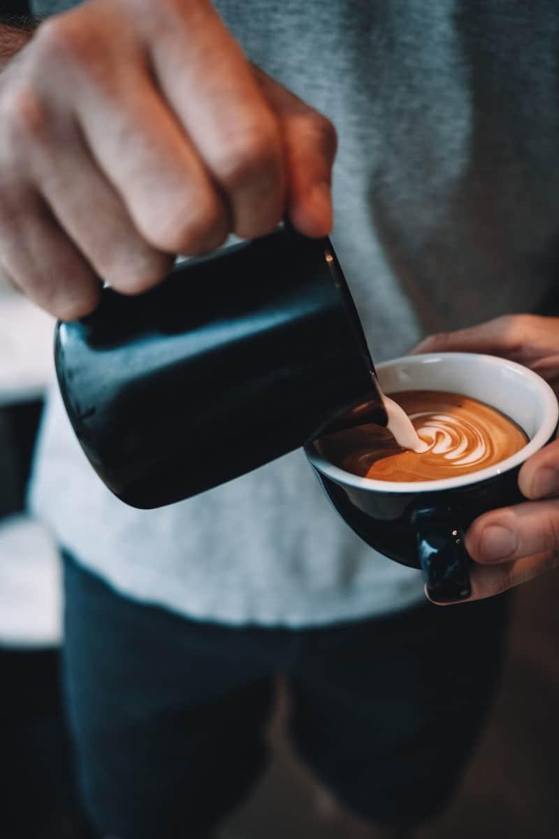 a barista pouring milk in espresso and making latte art