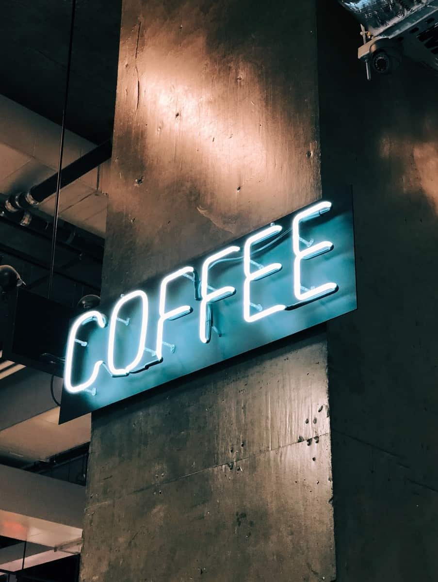 blue neon sign that says the word Coffee